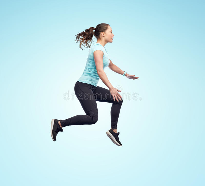 Happy smiling sporty young woman jumping in air. Sport, fitness, motion and people concept - happy smiling young woman jumping in air over blue background royalty free stock photos