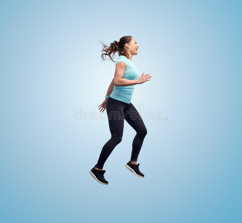 Happy smiling sporty young woman jumping in air. Sport, fitness, motion and people concept - happy smiling young woman jumping in air over blue background royalty free stock photo
