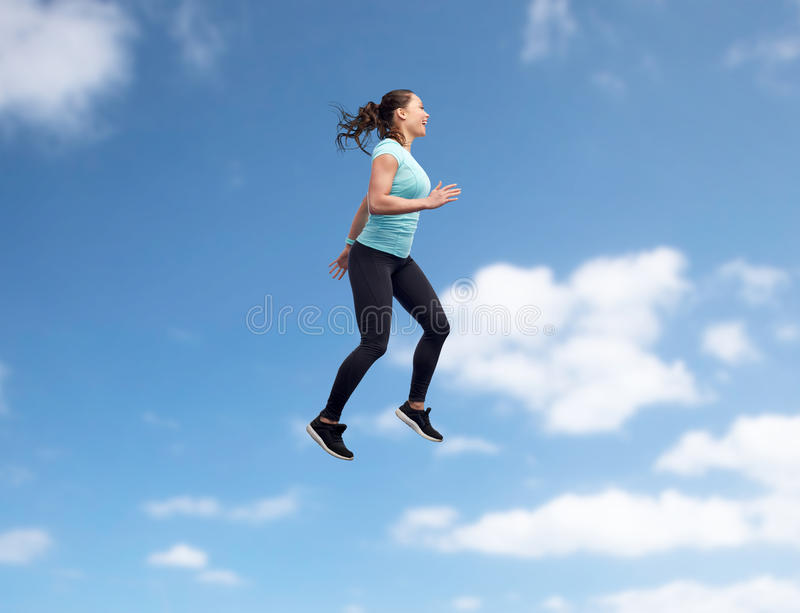 Happy smiling sporty young woman jumping in air. Sport, fitness, motion and people concept - happy smiling young woman jumping in air over blue sky background stock images