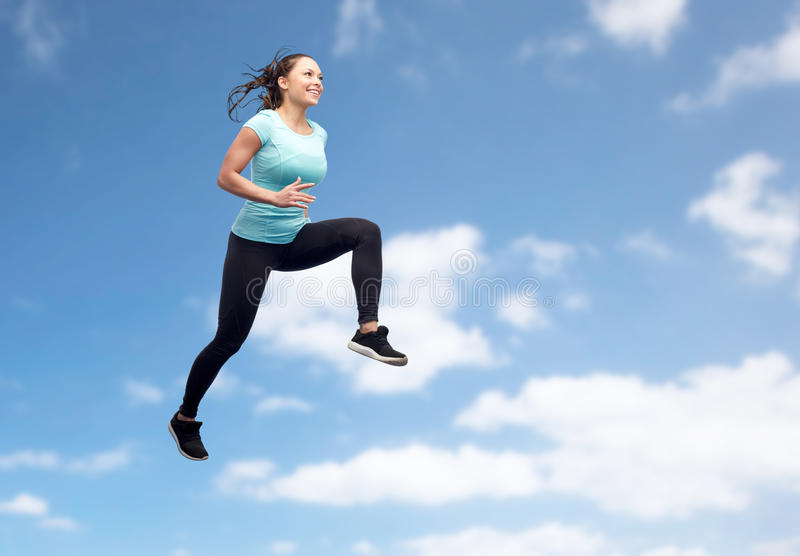 Happy smiling sporty young woman jumping in air. Sport, fitness, motion and people concept - happy smiling young woman jumping in air over blue sky and clouds royalty free stock photography