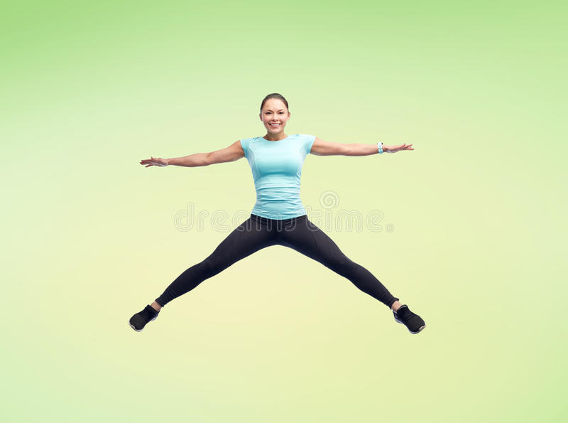 Happy smiling sporty young woman jumping in air. Sport, fitness, motion and people concept - happy smiling young woman jumping in air over green background royalty free stock photography
