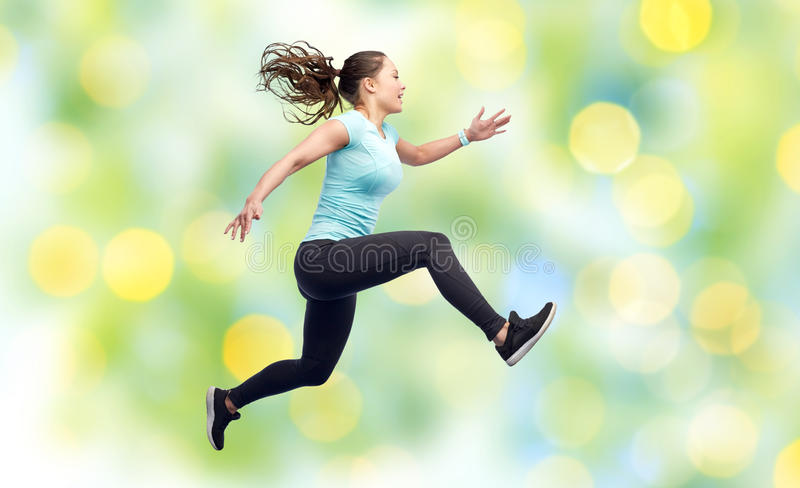 Happy smiling sporty young woman jumping in air. Sport, fitness, motion and people concept - happy smiling young woman jumping in air over summer green lights royalty free stock photos