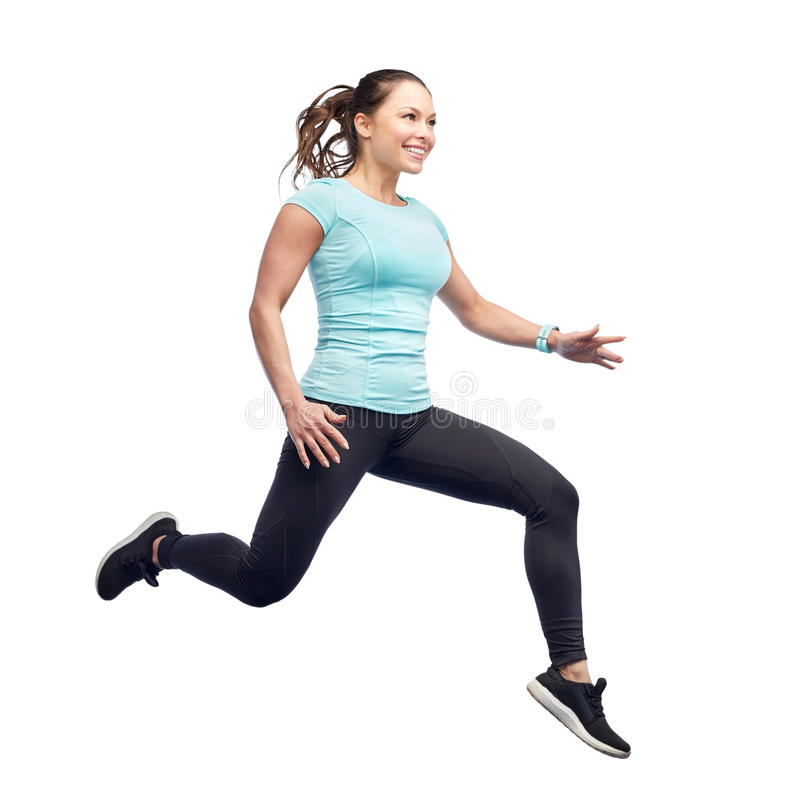 Happy smiling sporty young woman jumping in air. Sport, fitness, motion and people concept - happy smiling young woman jumping in air over white background royalty free stock image