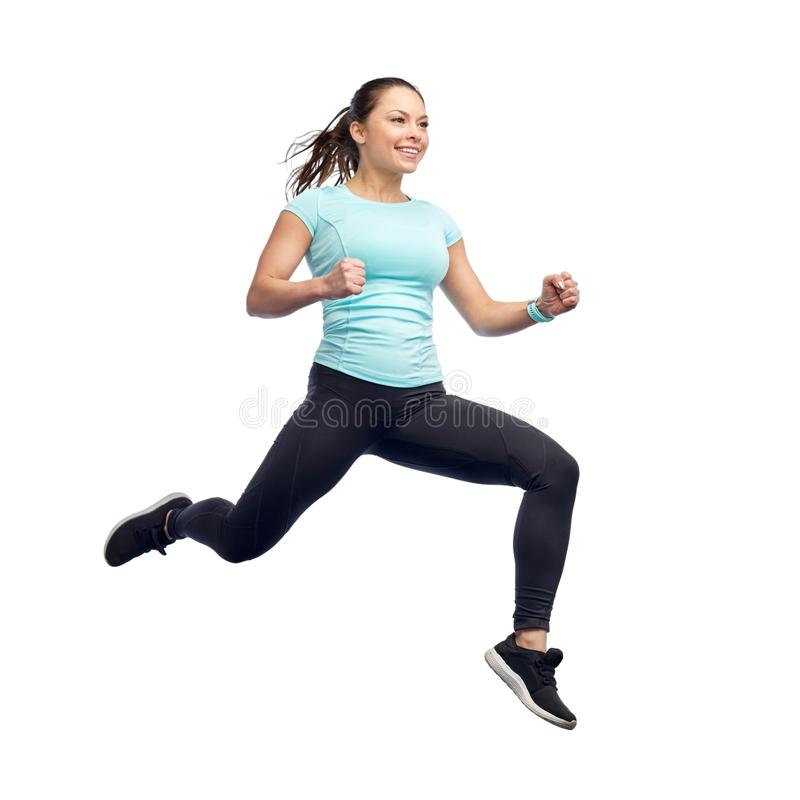 Happy smiling sporty young woman jumping in air. Sport, fitness, motion and people concept - happy smiling young woman jumping in air over white background royalty free stock images
