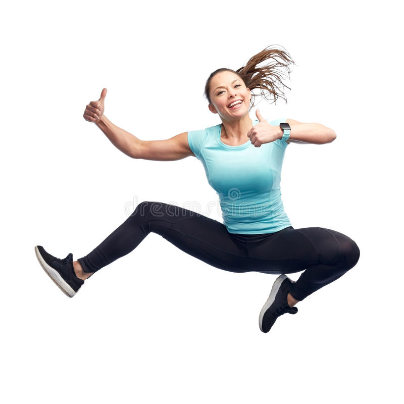 Happy smiling sporty young woman jumping in air. Sport, fitness, motion and people concept - happy smiling young woman jumping in air over white background royalty free stock photos