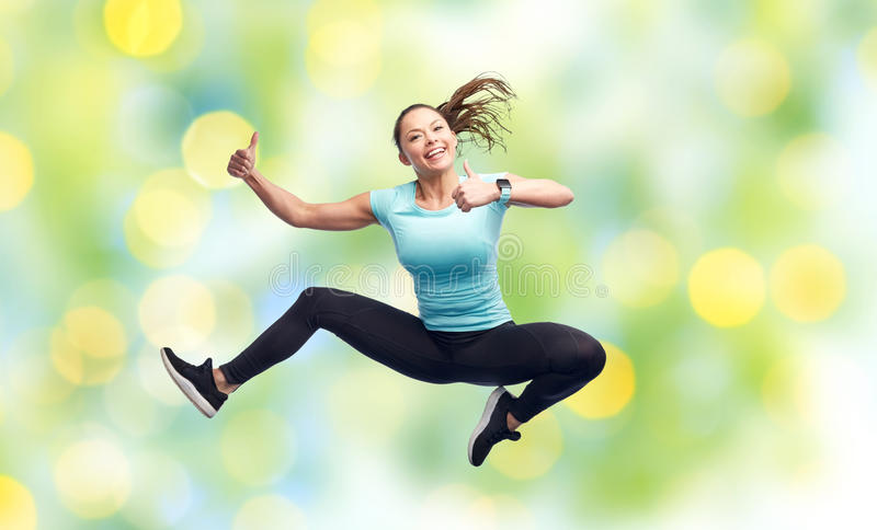 Happy smiling sporty young woman jumping in air. Sport, fitness, motion and people concept - happy smiling young woman jumping in air and showing thumbs up over stock photography