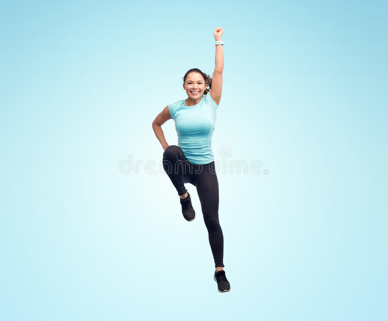Happy smiling sporty young woman jumping in air. Sport, fitness, motion and people concept - happy smiling young woman jumping in superhero pose over blue royalty free stock photography