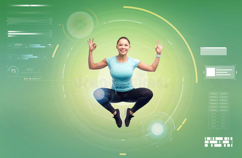 Happy smiling sporty young woman jumping in air. Sport, fitness, motion, technology and people concept - happy smiling young woman jumping in air and showing ok royalty free stock photo