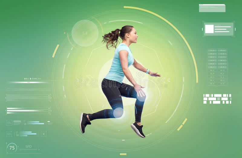 Happy smiling sporty young woman jumping in air. Sport, fitness, technology, motion and people concept - happy smiling young woman jumping in air over white royalty free stock photo