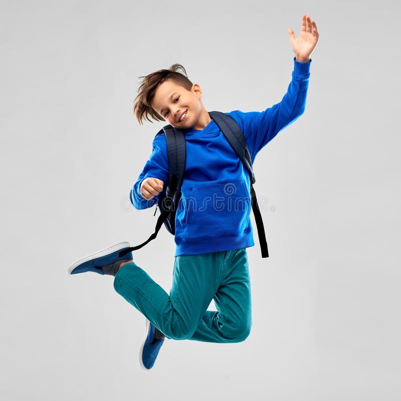 Happy smiling student boy with school bag jumping royalty free stock images