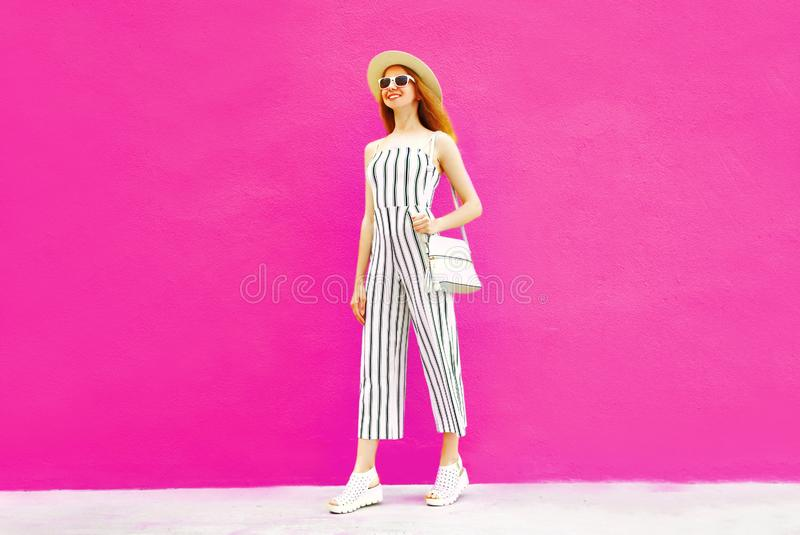 Happy smiling stylish woman in summer round straw hat, white striped jumpsuit on colorful pink wall. Background royalty free stock photography