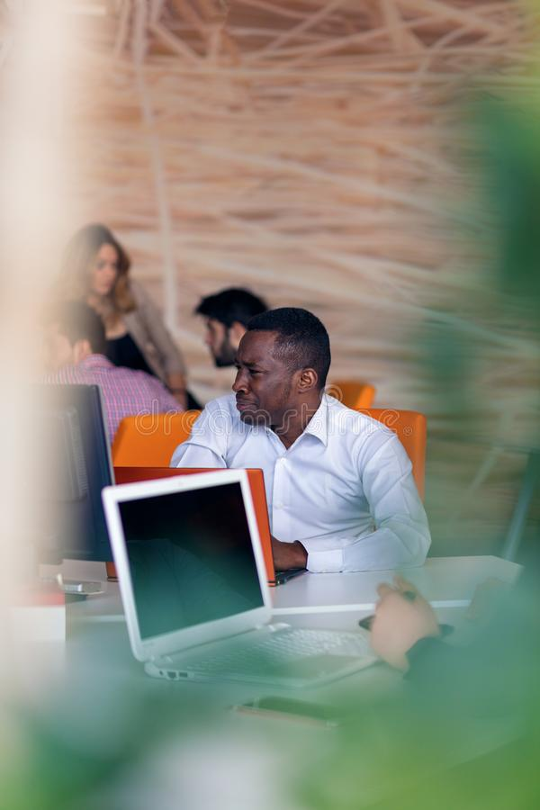 Happy smiling successful African American businessman in in a modern bright startup office indoors royalty free stock photo