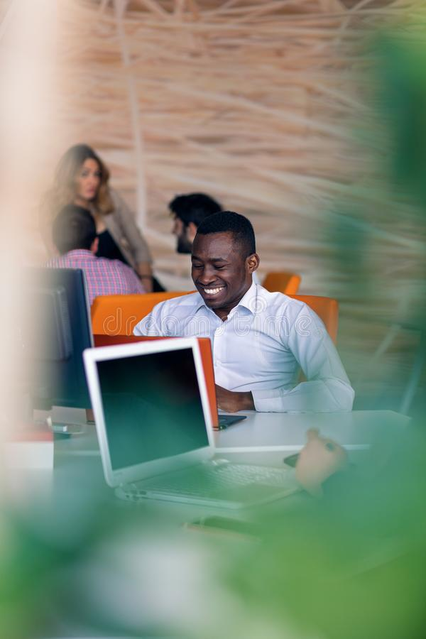 Happy smiling successful African American businessman in in a modern bright startup office indoors royalty free stock images