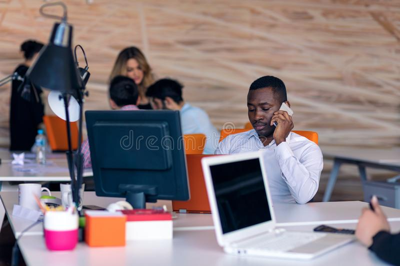 Happy smiling successful African American businessman in in a modern bright startup office indoors stock photography