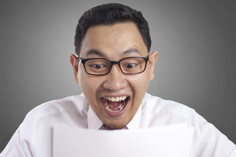 Happy Smiling Surprised Businessman Reading Positive Financial Report. Portrait of happy smiling successful Asian businessman shows surprised gesture for having stock photos