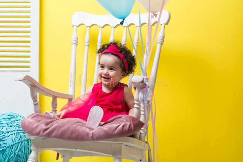 Happy smiling sweet baby girl sitting on armchair with birthday balloons royalty free stock photo