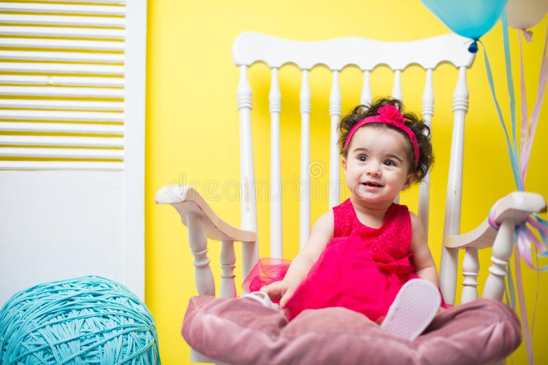 Happy smiling sweet baby girl sitting on armchair with birthday balloons royalty free stock photography