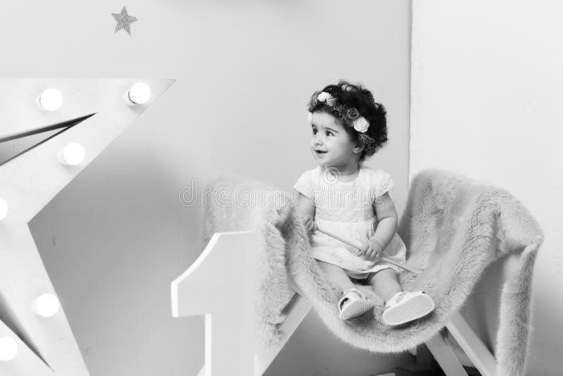 Happy smiling sweet baby girl sitting on armchair with shining light star, Birthday girl, One year old. Black and white photo royalty free stock photos