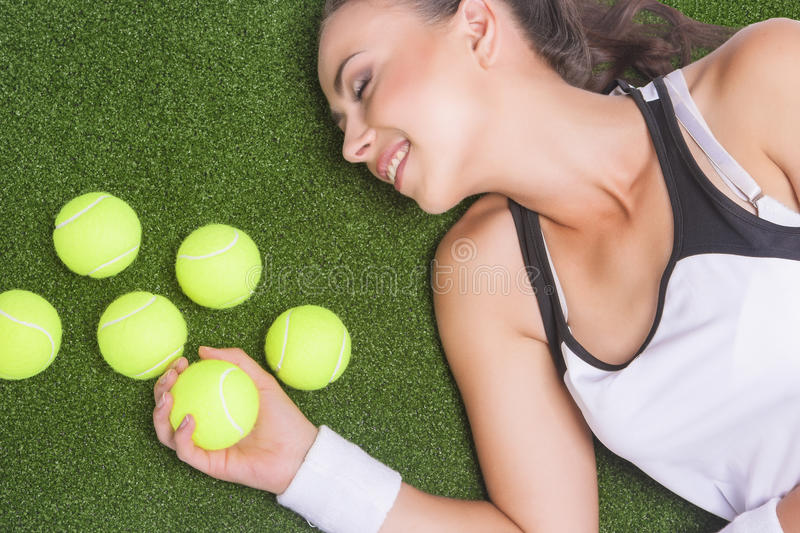 Happy Smiling Tanned Female Sportswoman Lying on Artificial Grass Surface Holding Tennis Ball stock photo