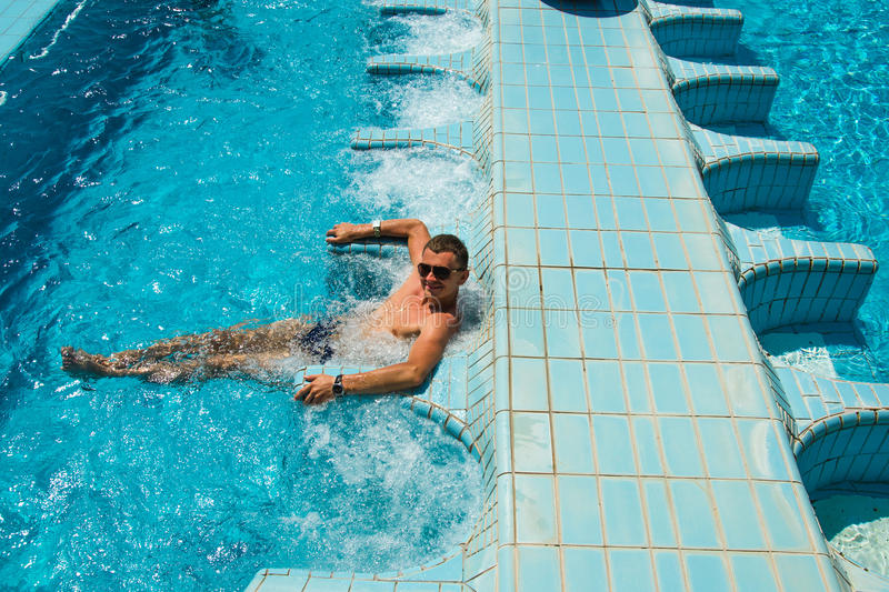 Happy smiling tanned man relaxing in pool jacuzzi outdoor at spa resort enjoying luxury life. Success, healthy lifestyle, body car royalty free stock images