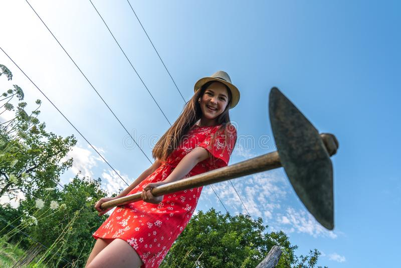 Happy smiling teen girl in red dress and hat pointing at the camera with spade, blue sky on the background, people and stock images