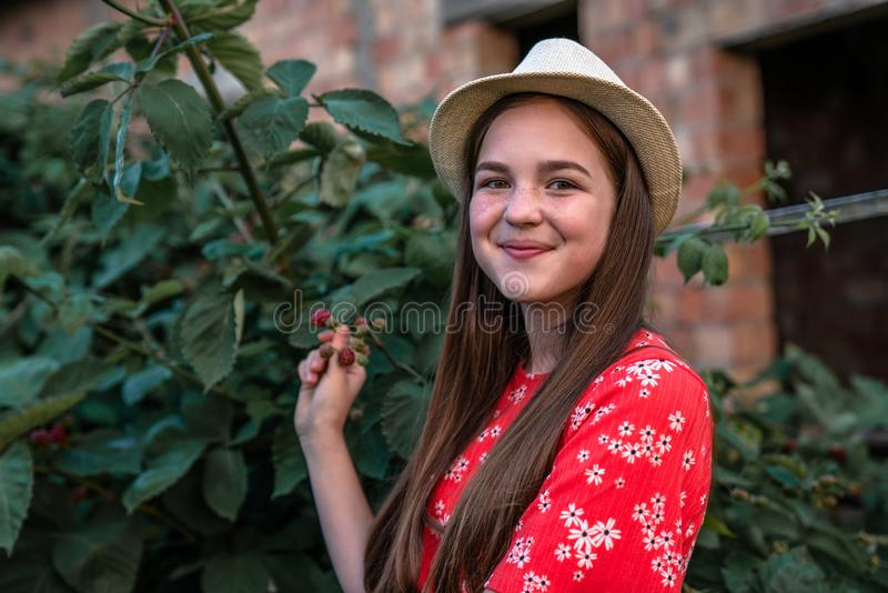 Happy smiling teen girl in red dress and hat standing near the bush of blackberry and looking at the camera, garden and stock photos