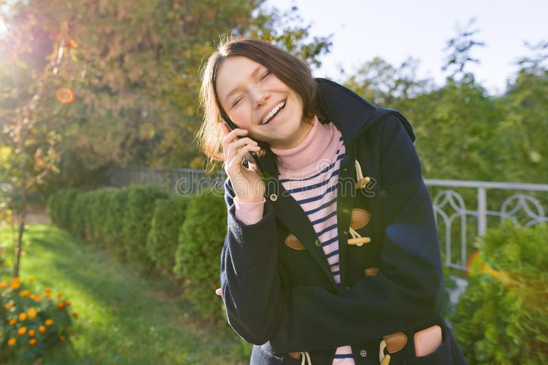 Happy smiling teenage girl in coat talking on mobile phone royalty free stock photography