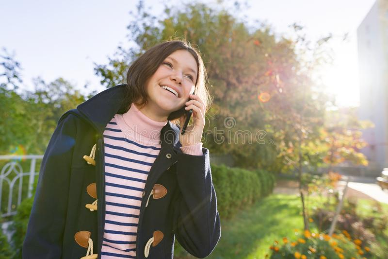 Happy smiling teenage girl in coat talking on mobile phone royalty free stock photos