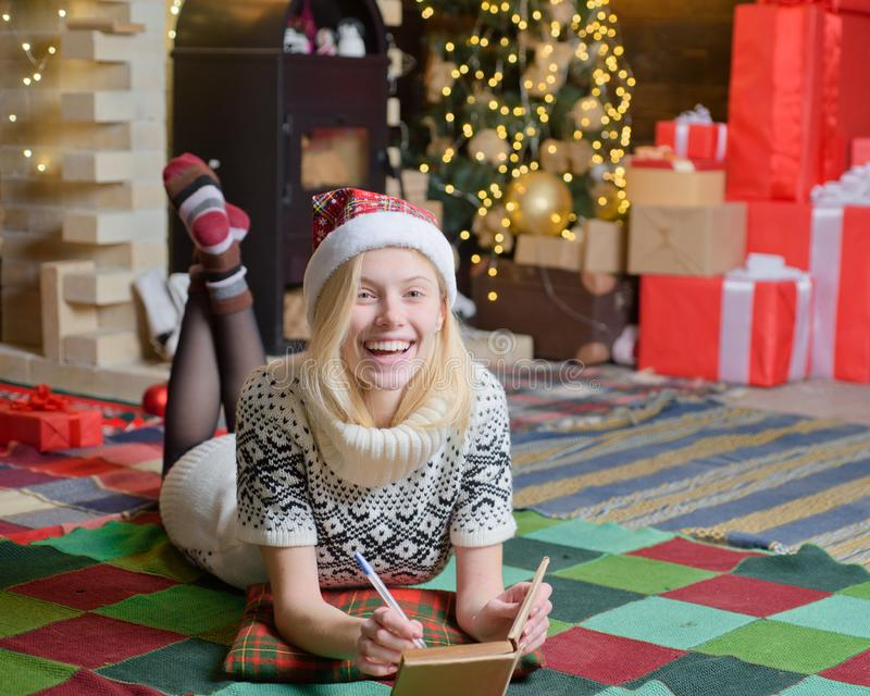 Happy smiling teenage girl in cozy warm clothes dream about new year presents and write a letter to Santa. Christmas eve royalty free stock images