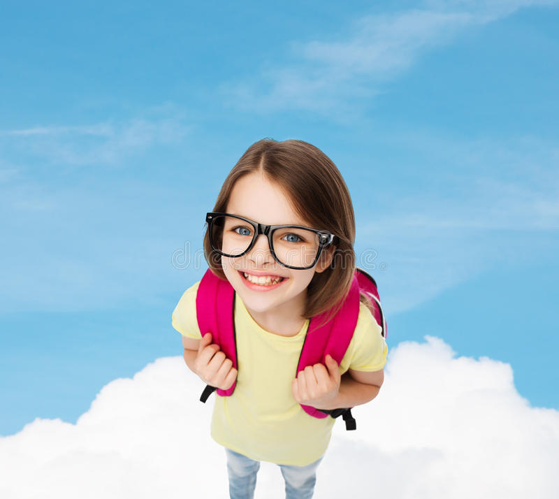 Happy smiling teenage girl in eyeglasses with bag. Education and school concept - happy and smiling teenage girl in eyeglasses with bag royalty free stock photos