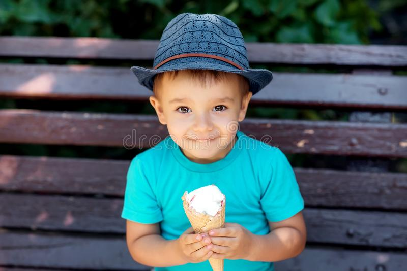 Happy smiling toddler boy in blue hat an shirt sitting on bench and holding with two hands ice-cream in waffle cone. Portrait of a happy smiling toddler boy in stock images