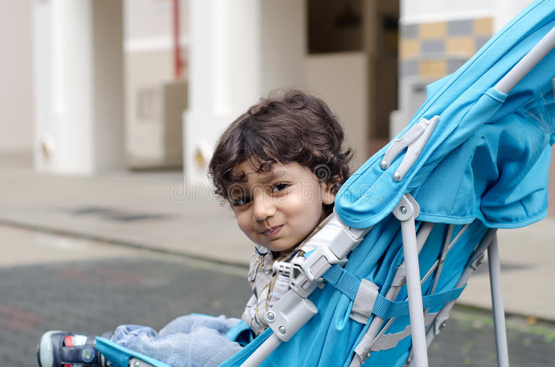 Happy smiling toddler child. Photo of a happy and smiling pre school (preschool) toddler boy child sitting in a blue stroller and staring at you stock photography
