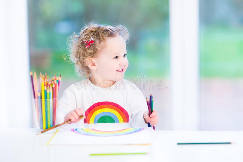 Happy smiling toddler girl drawing a rainbow. Next to a big window royalty free stock photography