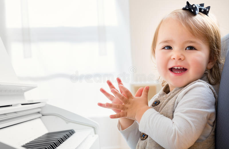 Happy smiling toddler girl excited to play piano stock photo