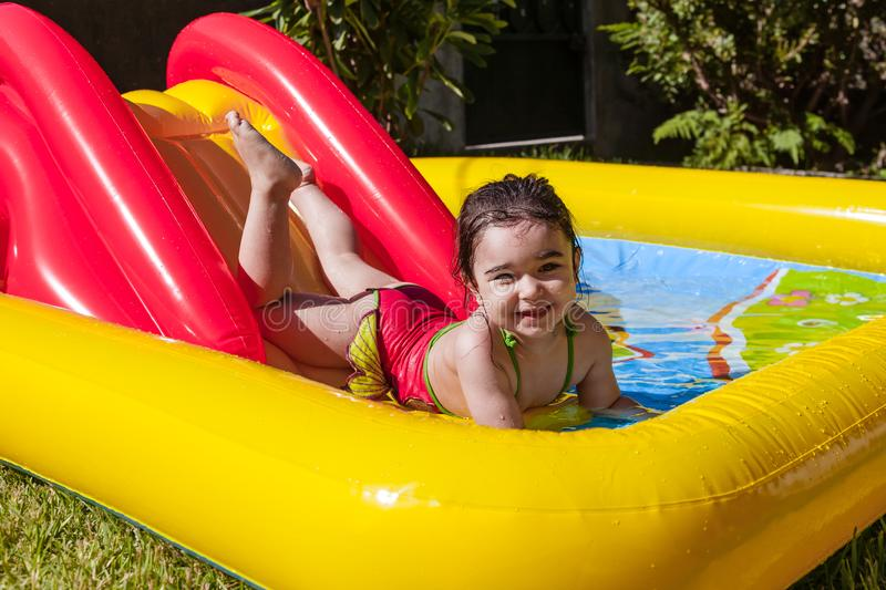 Happy, smiling toddler, playing and splashing in slider of colorful inflatable stock images