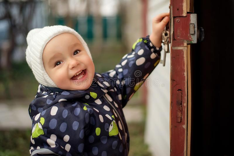 Happy smiling toddler in white woolen hat opening old door to somewhere. Children safety concept. Portrait of a happy smiling toddler child in white woolen hat royalty free stock photos