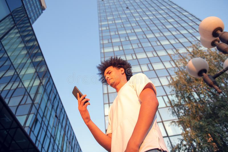 Happy smiling urban hipster young man using smart phone. African american teenager holding mobile smartphone on sunset royalty free stock photo