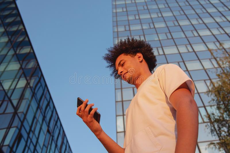 Happy smiling urban hipster young man using smart phone. African american teenager holding mobile smartphone on sunset royalty free stock photography