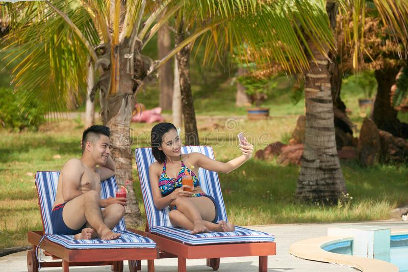 Couple resting by pool royalty free stock photo