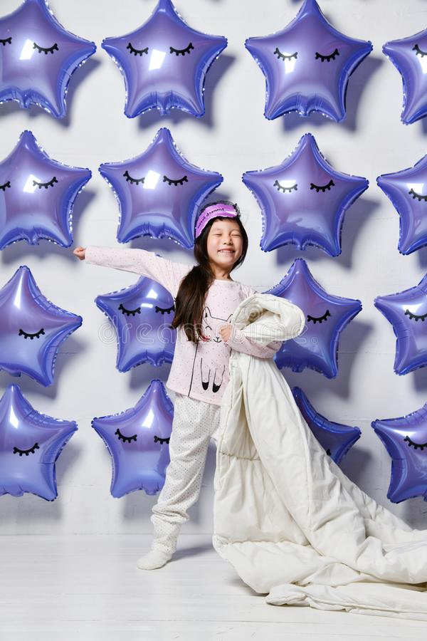 Happy smiling well-slept asian girl kid stands with her blanket and stretches in the morning on background of big balloons stars. Happy smiling well-slept asian stock image
