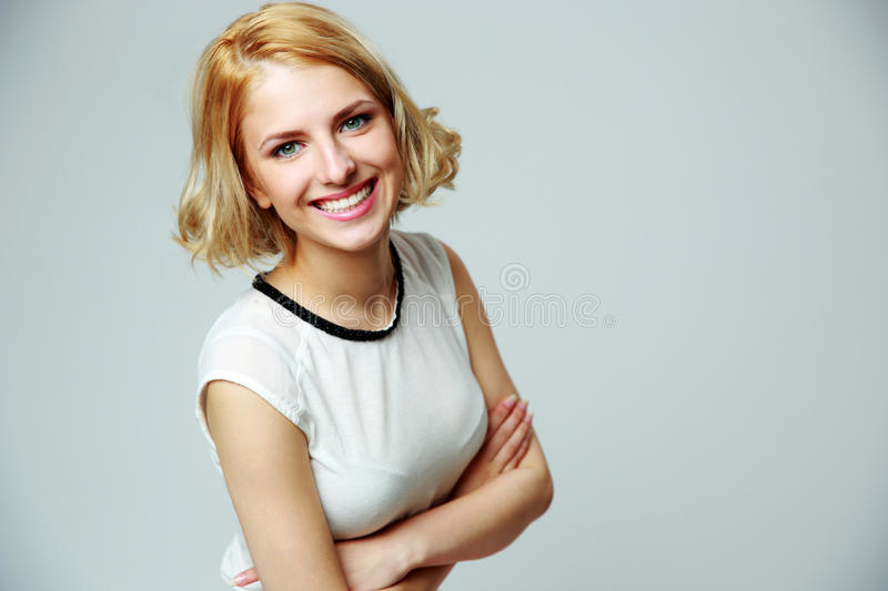 Happy smiling woman with arms folded. Portrait of a happy smiling woman with arms folded on gray background stock photography