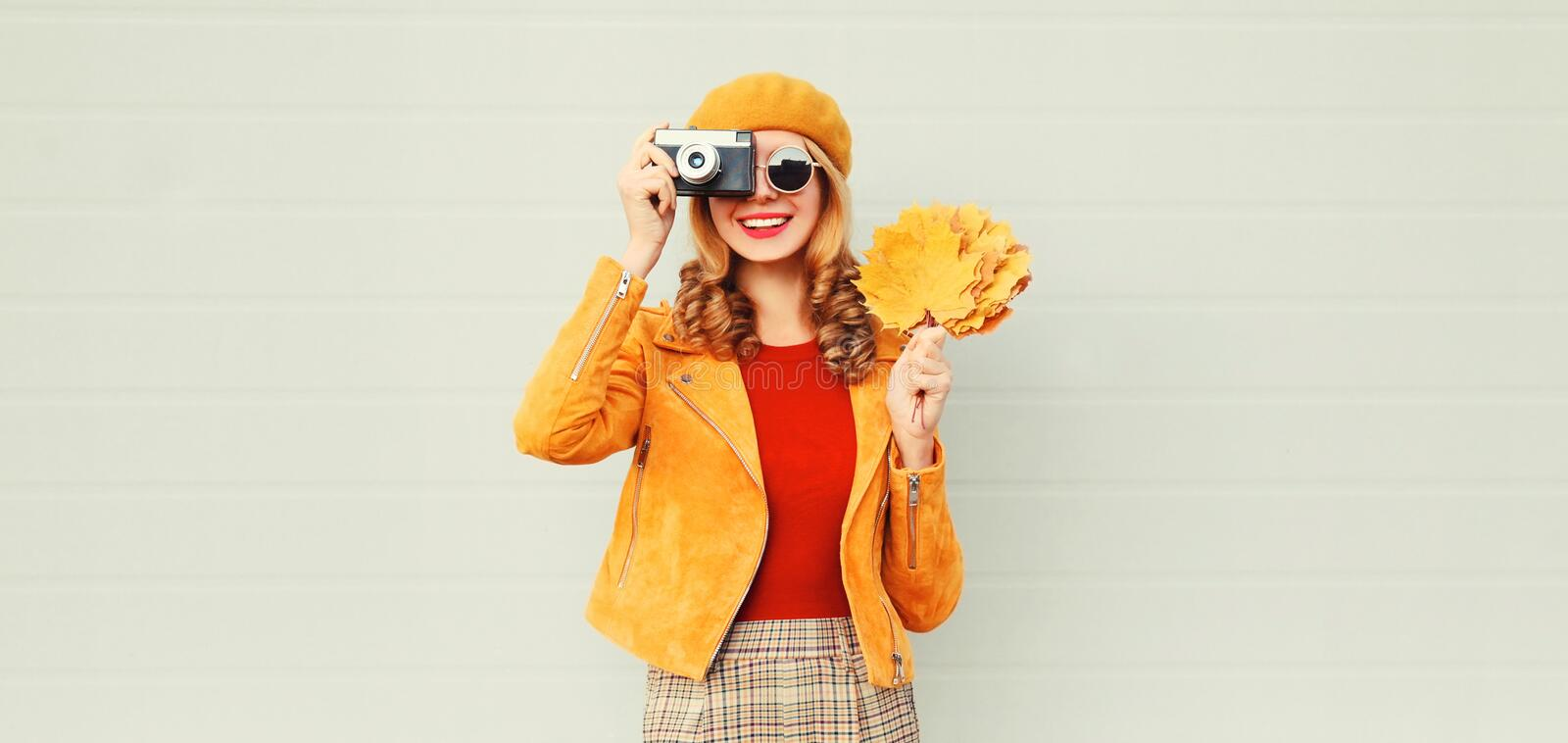 happy smiling woman with autumn yellow maple leaves, retro camera taking picture in french beret over gray wall stock image