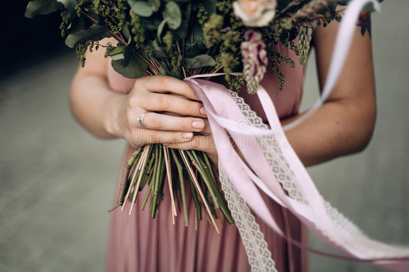 Happy and smiling woman with bouquet of flowers in a pink wedding dress and wedding ring. Bride, Bridesmaid. Modern photo style stock images