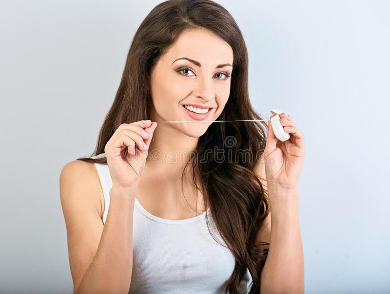 Happy smiling woman cleaning the teeth the dental floss on blue background with empty space. Dental Hygiene stock photo