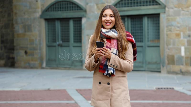 Happy smiling woman with coat and scarf using smart phone in city street, looking at camera. Copy space royalty free stock photography
