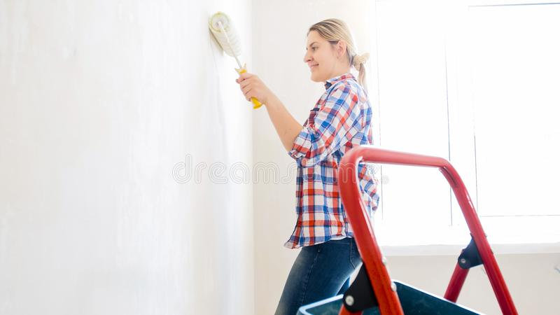 Happy smiling young woman doing renovation and painting walls with paint roller royalty free stock photos