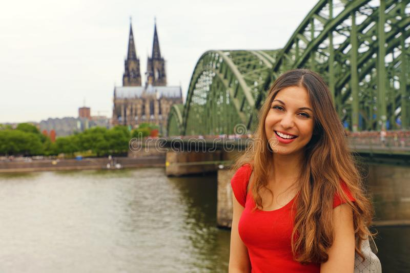 Happy smiling woman enjoying her travel in Germany. Beautiful traveler girl posing in front of the camera with Cologne Cathedral royalty free stock photos