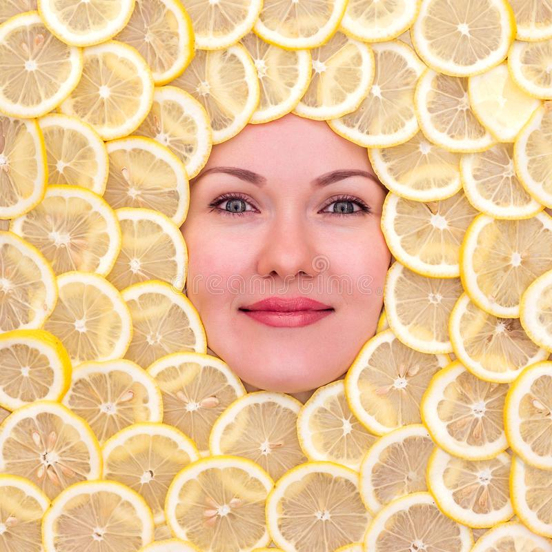 Happy smiling woman face surrounded by juicy sliced lemons. Freshness, healthy diet, vitamins and energy and wellness concept. Happy smiling woman face stock photography
