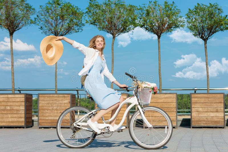 Woman is cycling in blue dress on white bicycle with basket of flowers stock photography