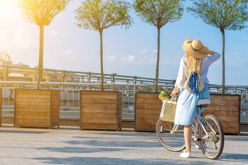 Woman in retro blue dress riding white bicycle on sunset royalty free stock images
